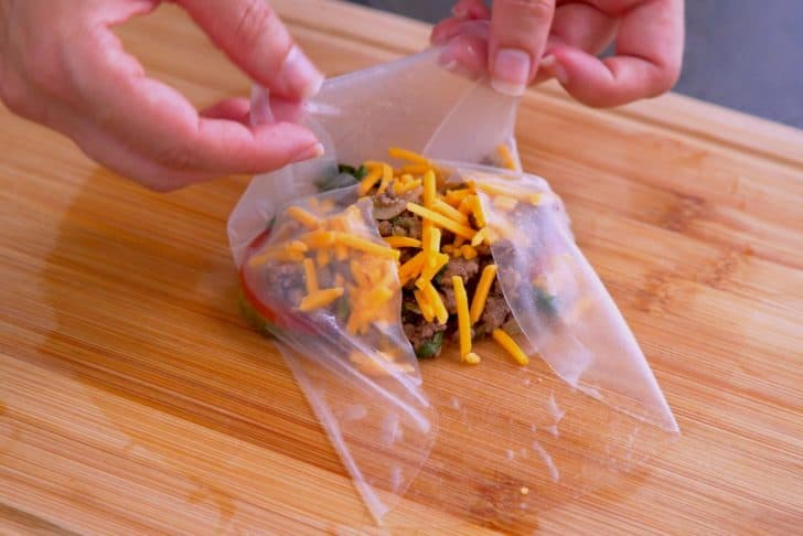 Layer filling ingredients onto wet rice paper, then fold in edges and roll up snugly.
