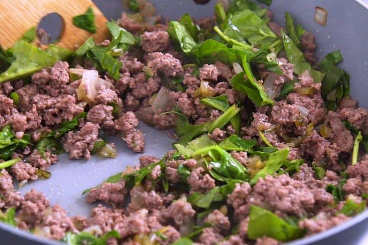Cook ground beef and combine with relish, spinach, and seasonings.