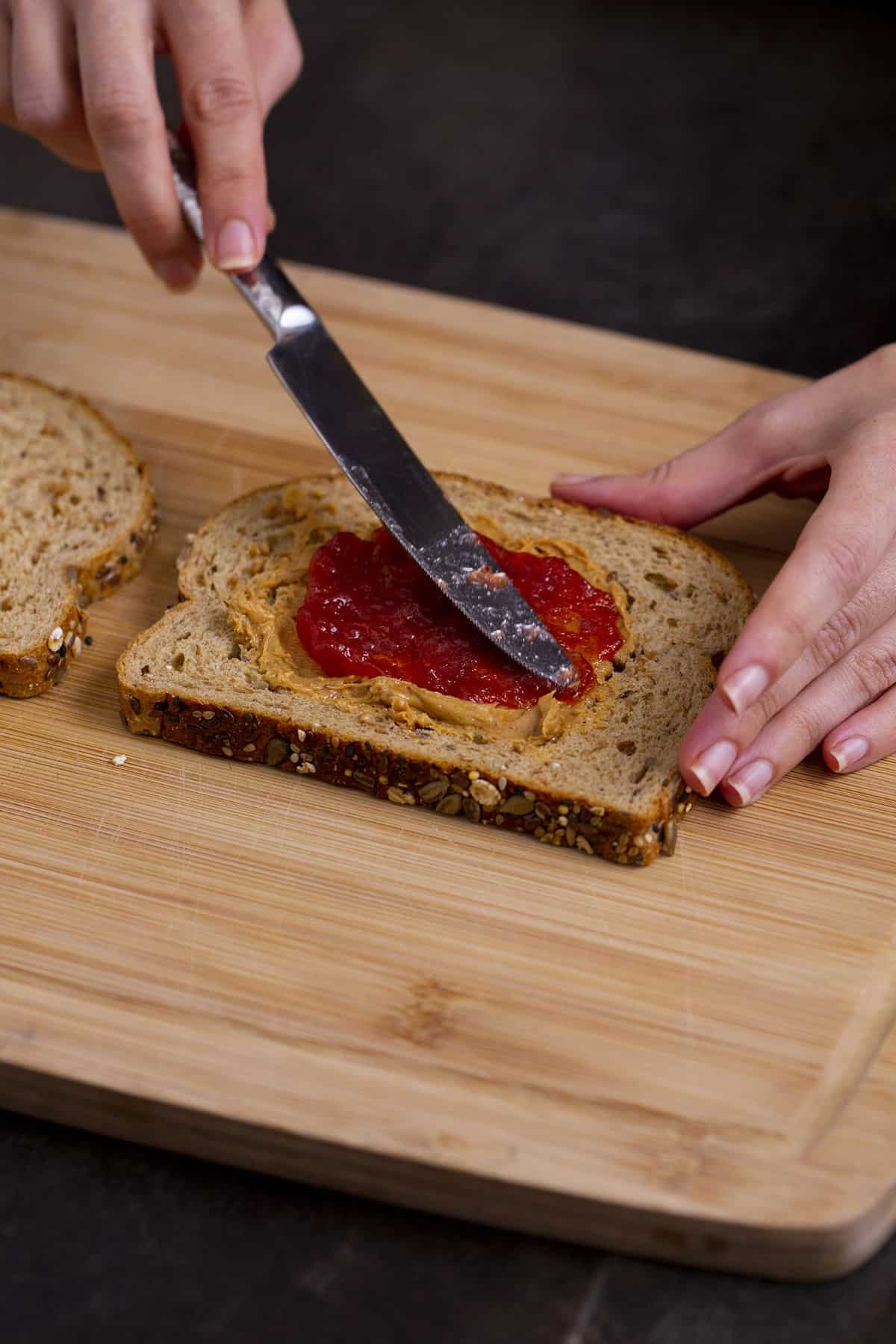Spread peanut butter and then jelly onto the same slice of bread, keeping both spreads in the center of the bread.