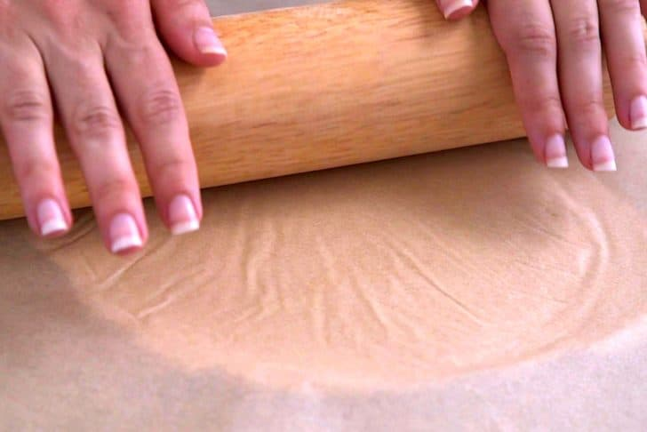Place another sheet of parchment on top of dough and roll out with a rolling pin, until ~⅛-inch thick.