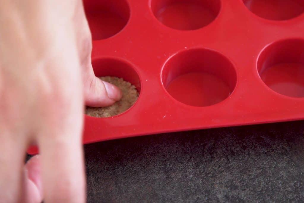 Press gluten free pumpkin cheesecake crust into bottom of desired molds.