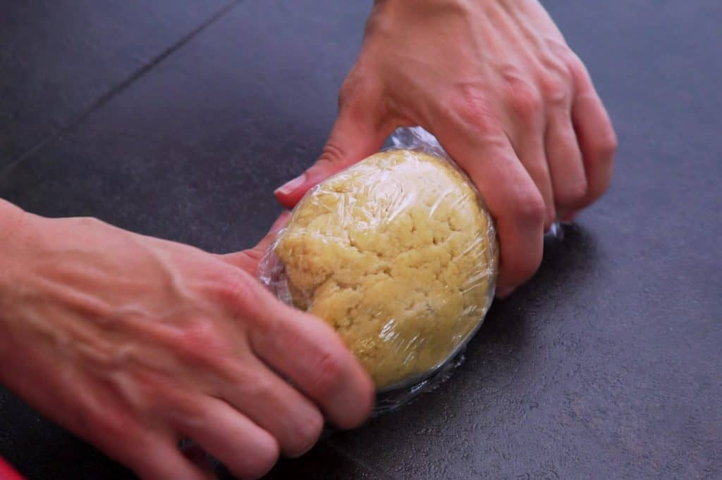 Shape keto tortillas dough into a ball, wrap in plastic, and refrigerate for at least 15 minutes.