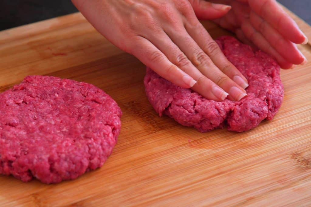 Shape meat gently, adding a shallow dimple in the center of each patty to prevent shrinkage and doming.