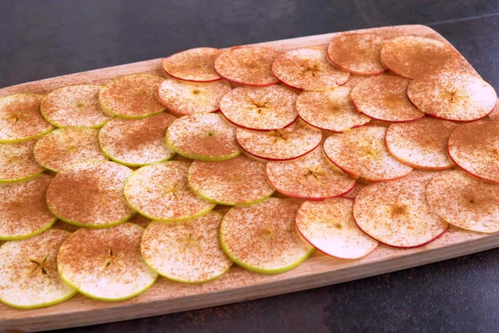 Lay out apple slices and sprinkle with cinnamon, to taste.
