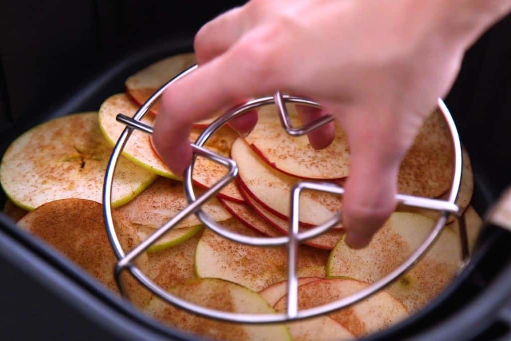Place a metal rack/trivet on top of apple chips in air fryer while they cook. Flip them every 5 minutes or so.