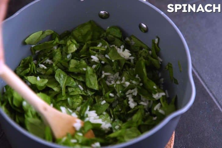 Add chopped spinach to cooked rice, cover, and allow to wilt.