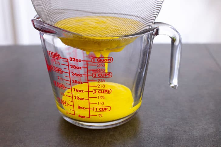 Strain blended juice through a fine mesh strainer, using a spatula to help move the juice through the strainer as needed.