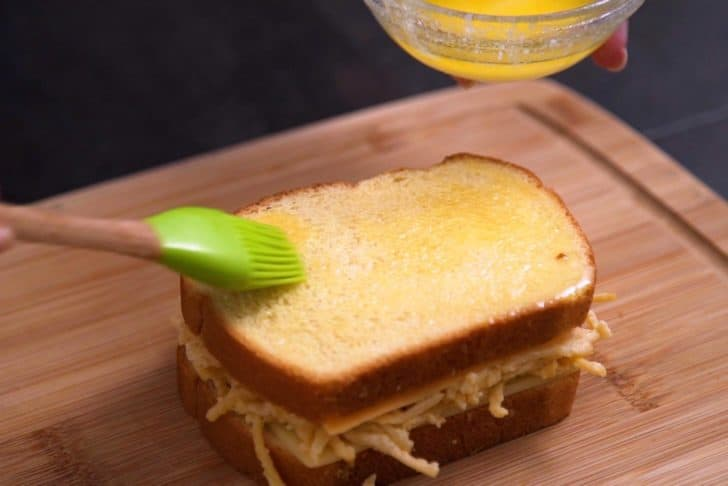 Brush melted butter onto bread before adding to hot pan or griddle.