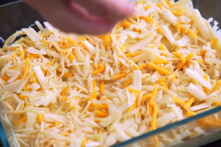 Transfer cheesy spaghetti to a casserole dish, cover with additional shredded cheese, and bake for 22-25 minutes.