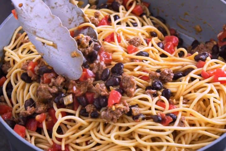 Toss cooked spaghetti noodles with taco mixture to combine.