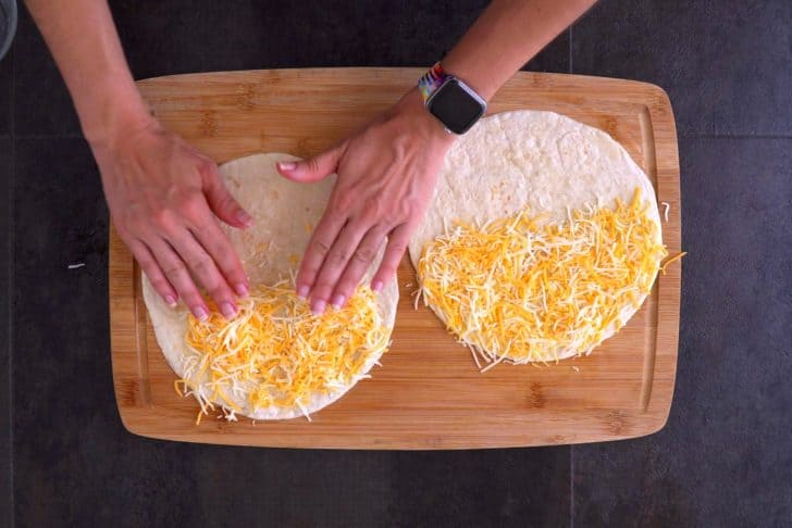 Flip tortilla so buttered side is down, then fill with cheese and any additional desired fillings.