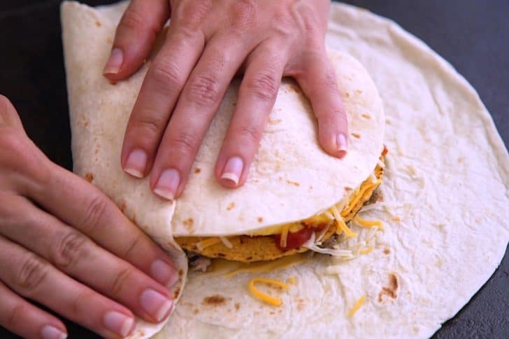 Place a small tortilla circle on top of cheese, then begin folding up edges of the large tortilla.