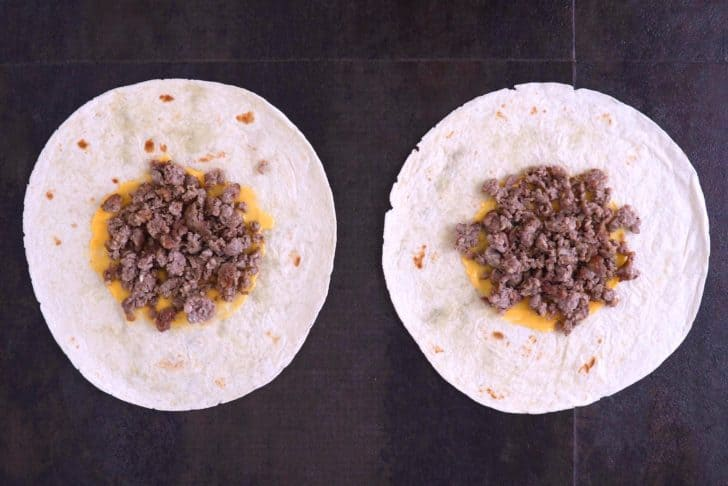 Lay large tortillas flat, spread nacho cheese sauce in the middle, and top with cooked breakfast sausage.