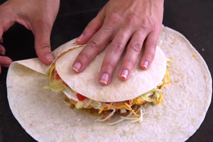 Place small tortilla circle on top of cheese and begin to fold up the edges of the large tortilla.