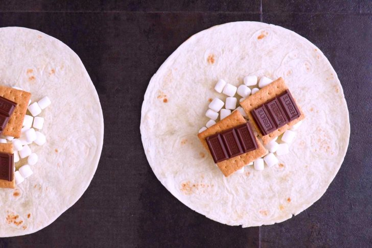 Layer marshmallows, graham crackers, and chocolate pieces onto center of tortilla.