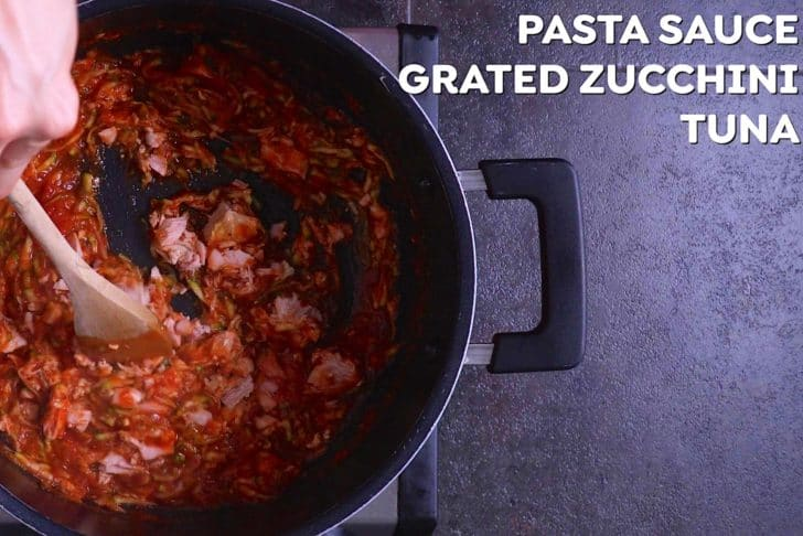 Heat pasta sauce and grated zucchini for 2-3 minutes, then add canned tuna to soften.