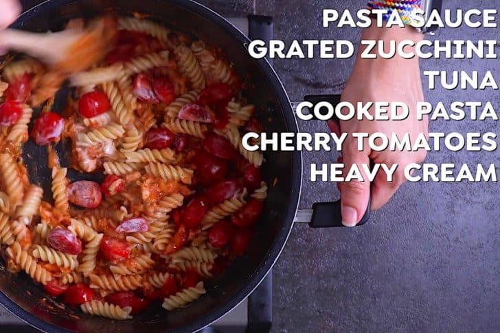 Add cooked pasta into sauce along with cherry tomatoes and a splash of cream, stirring to integrate.