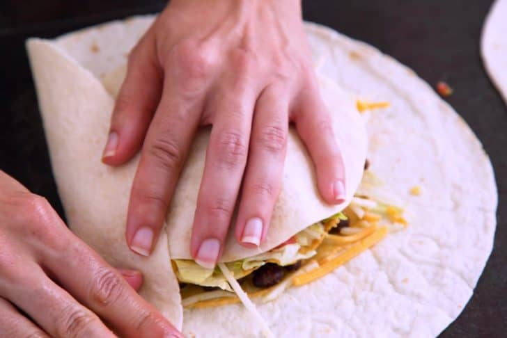 Place a small tortilla circle on top, then begin folding in the edges of the large tortilla.