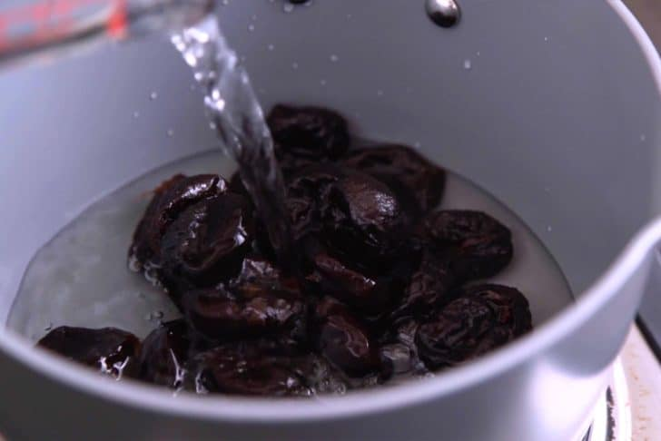 Add prunes and water to a saucepan over low heat.