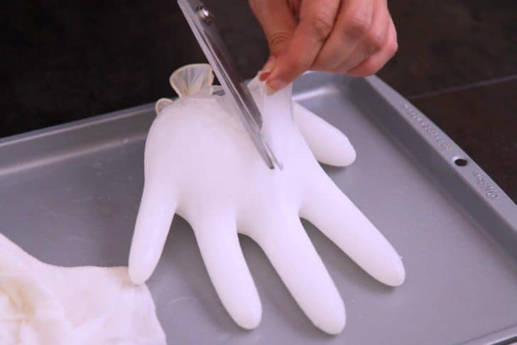Once frozen, wipe outside of glove with a warm, wet paper towel to help loosen the ice from the glove. Cut the knot at the top, then cut away the rest of the glove to separate it from the ice.